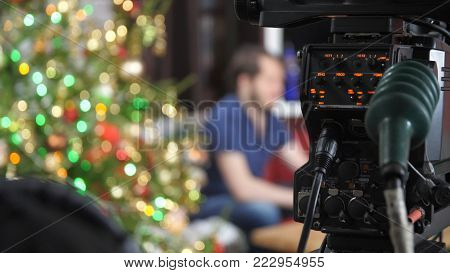 Video camera operator working with his equipment. Operator removes the camera Christmas show. Man filming.