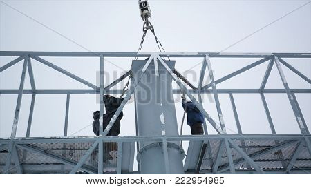 Builder on a Lift Platform at a construction site. Men at work. construction worker assembling scaffold on building site. Men assemble Billboard on tap.