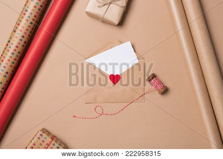 Gift Wrapping Background. Flat Lay. Top View.  Close-up. Craft Envelope With Red Heart, Blank Paper,