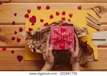A creative person packs a handmade gift in a beautiful red box tied with a ribbon. Creation. Celebrating the event.