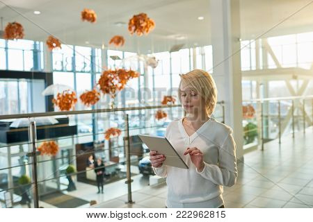 Concentrated blond-haired white collar worker using digital tablet while standing at spacious office lobby with panoramic windows, portrait shot