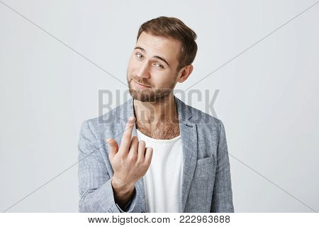 Handsome man with dark hair, stylish haircut, blue eyes, and beard looks with appeal at camera, isolated against gray background. Confident european gestures like says come here. Body language