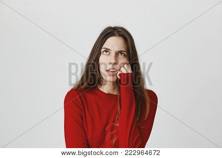 Indoor shot of pretty dark-haired woman making grimace, looking upwards, resting her head on hand, having tired and annoyed expression. Face expression and negative emotions