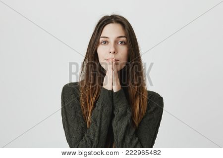 Pensive religious beautiful young woman holding hands in prayer hoping for fortune. Thoughtful young female begging for something, being deep in her thoughts. Body language and face expression