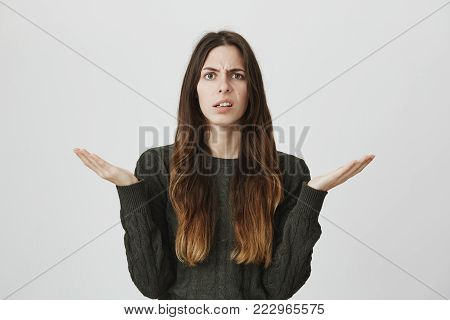 Portrait of unhappy confused and questioned attractive young girl holding her palms up, isolated over white background. Woman has no clue why her boyfriend is angry at her. Copy space