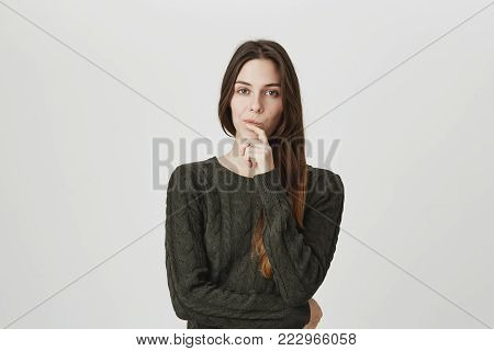 Indoor shot of thoughtful pretty woman has long dark hair, looks at camera with pensive expression, plans something on coming weekends, makes important decision, pouts lips, poses against gray background