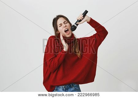 Gorgeous woman with long brown hair enjoying singing, holding a microphone over white background. Girl definitely knows how to perform. Coworkers amazed of her voice. Someday she will be a star. Emotions concept