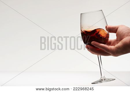 Testing red wine drink beverage. Elegant wine glass in hand close-up isolated on white background