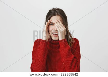 Portrait of young attractive woman with brown hair peeking while covering one eye with hand, isolated over white background. Girl feels embarrassed though she is interested so she keeps staring. Emotions concept