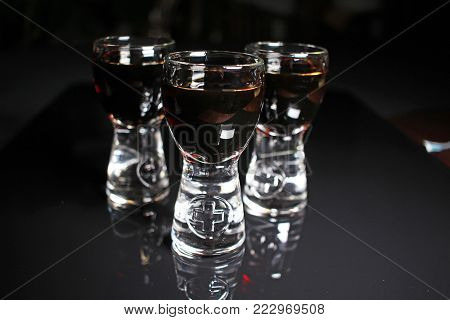 Rum shots. Alcohol shot brown dark rum on black reflective studio background. Isolated black shiny mirror mirrored background for every concept. Photo.