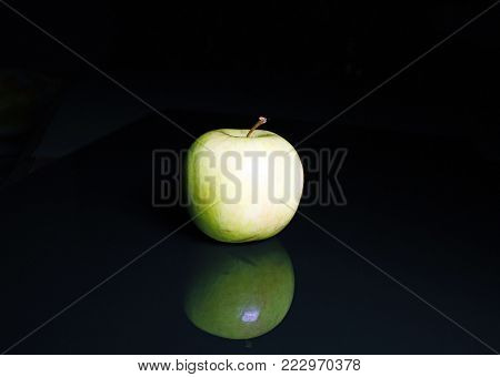 Apple. Green apple on black reflective studio background. Isolated black shiny mirror mirrored background for every concept. Green apple.