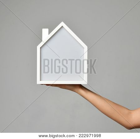 Property Investment concept. Woman hand hold house symbol of real estate money investment on grey background