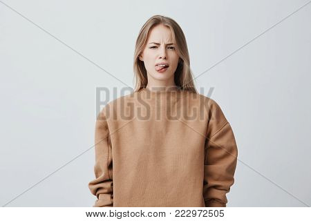 Naughty beautiful girl with blonde long hair in beige sweater misbehaving, sticking out her tongue at camera as a sign of disobedience, protest and disrespect. Human emotions, reactions, feelings and attitude