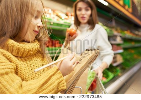 Side view portrait of little girl holding shopping list and ticking off items while grocery shopping in supermarket with her mother, copy space