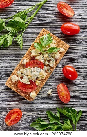 Crispbread with blue cheese and tomatoes, decorated with potherb on wooden table