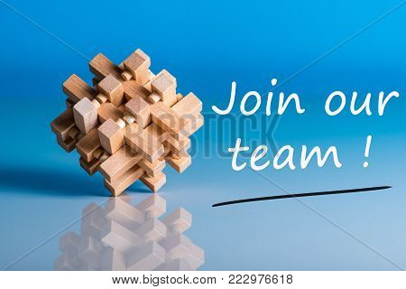 Job recruiting advertisement represented by 'JOIN OUR TEAM' texts on blue background with wooden brain teaser talking about the difficult tasks, new challenges and opportunities.