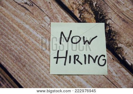 Now Hiring written on an yellow sticky note paper on the wooden oak background