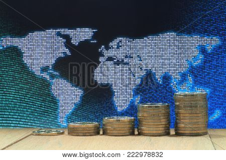 World of idea. Coin pile stacked in increasing chart shape on wood board with White dots grid pattern world map on digital blue and green color dot.