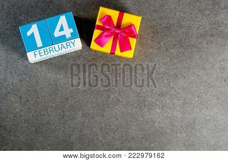 February 14th. Day 14 of february month, calendar on dark background with gift box. Saint Valentine's days. Empty space for text, mockup.
