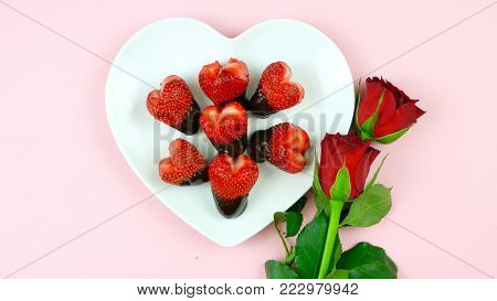 Happy Valentine's Day overhead flat lay with heart shaped strawberries dipped in chocolate.