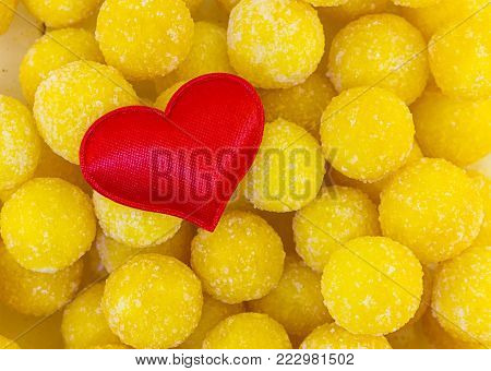 Symbol Of Love Family Red Heart Cloth On A Background Of Candied Yellow Candy Balls Sweet. Base Post