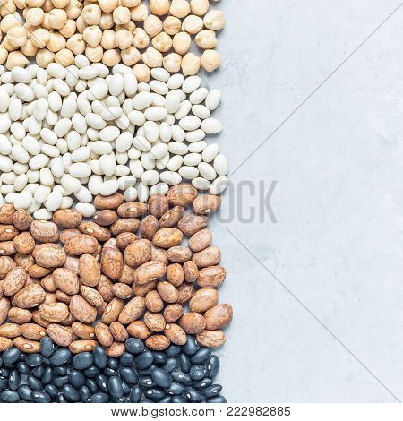 Different kinds of beans: black, pinto, white and chickpeas, on a concrete background, square format