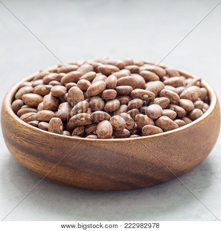 Uncooked dry pinto beans in a wooden bowl, square format