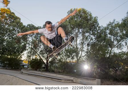 young American man practicing radical skate board jumping and enjoying tricks jumps and stunts in concrete half pipe skating track in sport and healthy lifestyle concept
