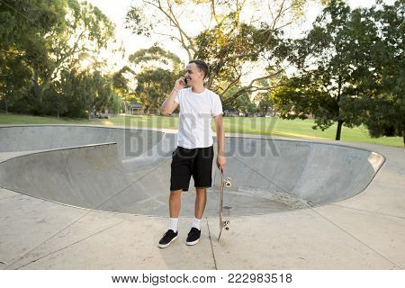 young happy and attractive American man 30s standing holding skate board after sport boarding training session talking on mobile phone in skateboarder conversation and communication