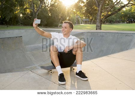 young happy and attractive American man 30s sitting on skate board after sport boarding training session taking selfie photo portrait or picture on mobile phone on sunset half pipe track park