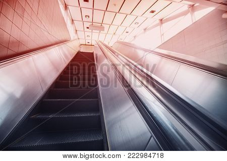 Escalator UNDERPASS. Ladder Moving Upwards to Light from an Underground Passage. Toning in red and blue.