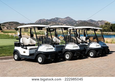 LAKESIDE, CALIFORNIA - JUNE 18, 2017:  A group of golf carts near a lake and distant mountains at Barona Creek Golf Club, at the Barona Resort and Casino in San Diego.