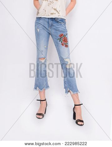 Front view Fashion. Woman legs in embroidered flowers,bird jeans and high heels shoes posing