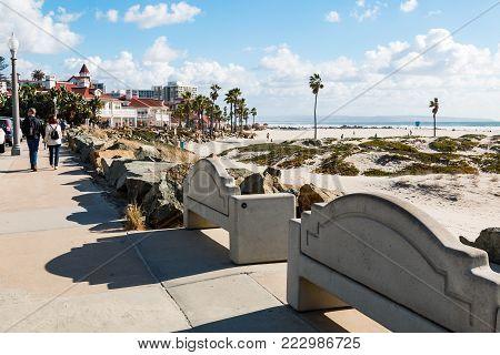 CORONADO, CALIFORNIA - JANUARY 20, 2018:  People stroll on the boardwalk on Coronado Central Beach, near the historic Hotel Del Coronado, a landmark in the San Diego area, built in 1888.