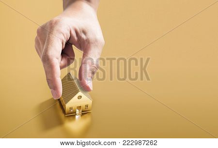 Hand picking golden house, real estate investment and buying home and property concept