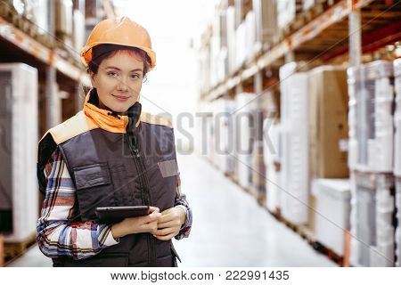 Woman with a clipboard in her hands is checking inventory levels in a warehouse. Smiling girl scrolling on digital tablet in a large warehouse time delivery concept photo.
