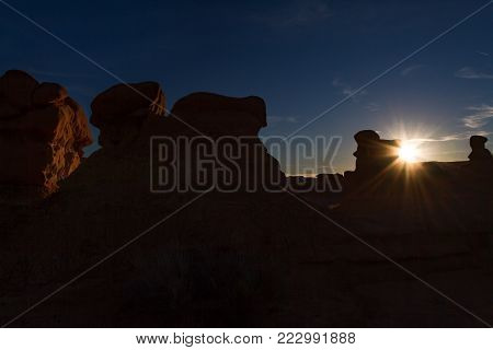 Sunset view of Goblin Valley State near Moab Utah with sunburst and glowing sandstone hoodoos.