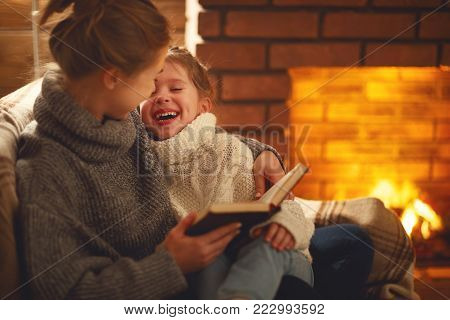 happy family mother and child daughter read a book on winter autumn evening near fireplace
