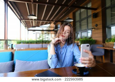 Pretty girl making selfie by smartphone at cafe with cup of coffee  . Young lady dressed in blue shirt looks gorgeous. Concept of snapshots by front facing camera.