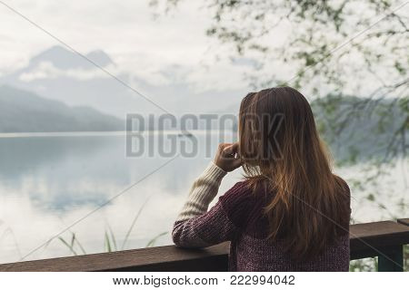 Lonely woman standing absent minded and looking at the river