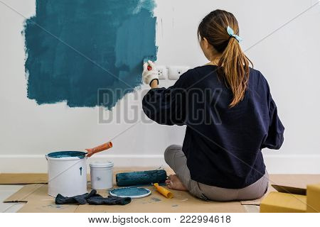 Young asian happy woman painting interior wall in new house