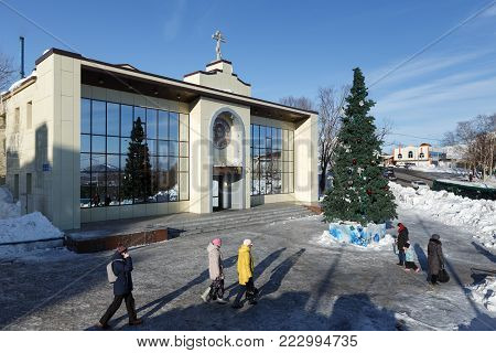 PETROPAVLOVSK, KAMCHATKA, RUSSIA - JAN 6, 2018: Diocesan Spiritual and Enlightenment Center of Petropavlovsk and Kamchatka Diocese of Russian Orthodox Church and Christmas tree in front of building.