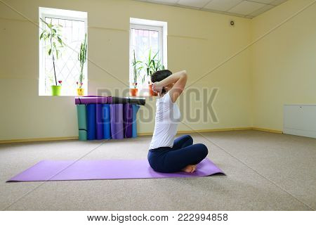 Beautiful young woman of American origin stands in middle of room on yoga mat and performs asanas standing on one leg. Girl dressed in sporty black tights and white T-shirt, hair is black and short cut. Concept of healthy lifestyle