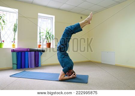 Young brunette of American origin sits on yoga mat and performs longitudinal twine. Short-haired sportswoman dressed in blue sports pants and blue t-shirt. Room light and spacious, under wall multi-colored yoga mats.