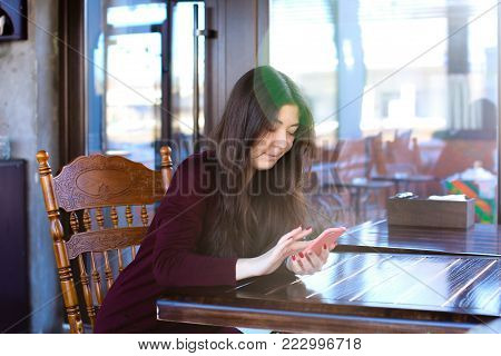 Manicurist replenish mobile account using smartphone and bank card, Asian girl sitting at wooden table near big window in coffee house with antique interior. Young woman with long fair hair and red manicure entering data