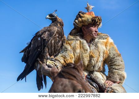 BAYAN-OLGII, MONGOLIA - SEP 30, 2017: Eagle Hunter at traditional clothing, while hunting to the hare holding a golden eagle, in mountains western Mongolia.