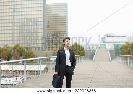 Lawyer in business clothes with smartphone waiting for client, man standing on bridge checking time on silver gadget. Middle-aged American with bag wearing strict suit looking by sides. Concept of fashionable man outfits, law services or innovative techno