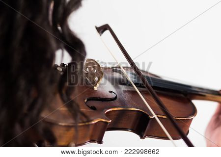 Girl playing the violin. The bow touches the strings. Close-up. View from the shoulder side through the hair. Musical theme. White background.