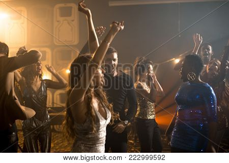 Group of trendy young people enjoying party in nightclub, beautiful girls wearing glittering clothes dancing on dance floor in smoky club