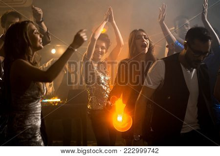 Crowd of trendy young people having fun in raving nightclub party, beautiful girls dancing on dim smoky dance floor